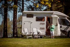 Woman is standing with a mug of coffee near the camper RV. royalty free stock images