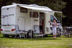 Woman is standing with a mug of coffee near the camper RV. stock images