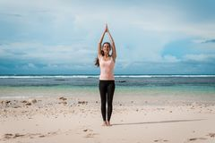 Woman standing a namaste yoga pose on the beach next to the ocean or sea in cloudy weather. Zen, meditation, peace. Sun