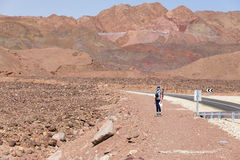 Woman standing near asphalt desert road. Stock Photo