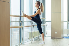 Woman standing near barre in fitness center Stock Photography