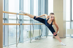 Woman standing near barre in fitness center Stock Photos