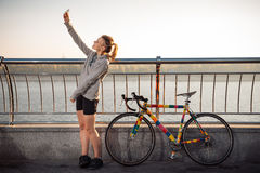 Woman standing near bicycle and making selfie Royalty Free Stock Images