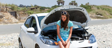 Woman is standing near broken car Stock Images