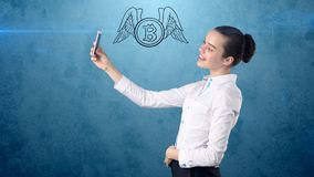 Woman standing near btc logo. Concept of virtual criptocurrency bitcoin dawnfall and correction. Beauty business woman standing near btc logo. Concept of Stock Photo