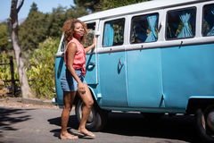 Woman standing near campervan in park. On a sunny day royalty free stock photo