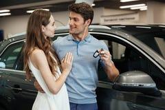 Woman standing near car with boyfriend in car dealership Stock Photo