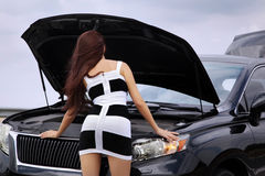 Woman standing near car with an open hood Royalty Free Stock Photo
