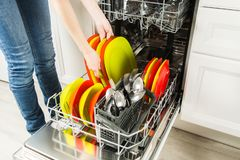 Woman is standing near dishwasher and taking clean plate from it royalty free stock photography