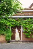 Woman standing near doors. Romantic woman standing near old doors under a bush of blossoming bougainvillea Royalty Free Stock Photography
