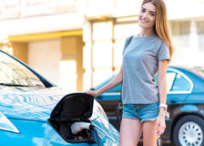 Woman standing near eco car Stock Image