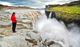 Woman standing near famous Dettifoss waterfall in Vatnajokull National Park, Iceland Stock Photography