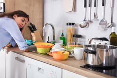 Woman Standing Near Kitchen Sink Looking At Utensils. Tired Young Woman Standing Near Kitchen Sink Looking At Utensils In Kitchen stock images