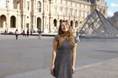 Girl standing near Louvre Pyramid and smiling. Royalty Free Stock Photos