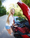 Woman standing near the opened hood of the broken cabriolet Royalty Free Stock Image