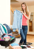 Woman standing near opened  suitcase. Beautiful young woman standing in the room near opened overfull suitcase Stock Image