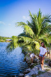 Woman standing near palm trees and a pond Stock Photography
