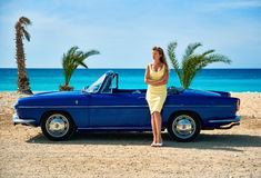 Woman standing near retro cabriolet car Stock Photos