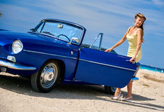 Woman standing near retro cabriolet car Stock Images