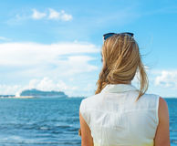 Woman standing near the sea. Stock Images