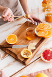 Woman standing near table with citruses and holding honey. Royalty Free Stock Photography