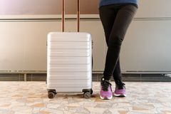Woman standing near travel luggage waiting flight in modern terminal royalty free stock image