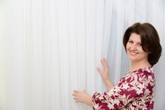 Woman is standing near tulle white curtains Royalty Free Stock Photography