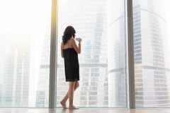 Woman standing near the window Stock Photos