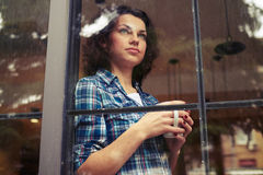 Woman standing near the window, holding cup of coffee Royalty Free Stock Photos
