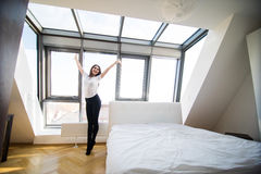 Woman standing near the window. While stretching near bed Royalty Free Stock Images