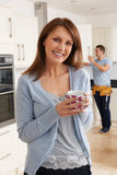 Woman Standing In New Fitted Kitchen With Workman. Woman Stands In New Fitted Kitchen With Workman Stock Images