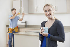 Woman Standing In New Luxury Fitted Kitchen Stock Image