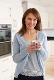 Woman Standing In New Luxury Fitted Kitchen Stock Photos