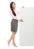 Woman standing next to big white poster. Young woman over white background Stock Images
