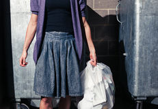 Woman standing next to bins with a bag of rubbish Stock Photography
