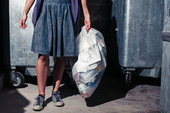 Woman standing next to bins with a bag of rubbish Royalty Free Stock Images