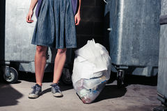 Woman standing next to bins with a bag of rubbish Royalty Free Stock Image