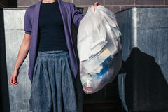 Woman standing next to bins with a bag of rubbish Stock Photo
