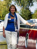 Woman standing next to a boat Stock Image