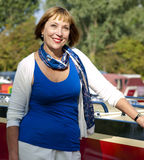 Woman standing next to a boat Stock Images
