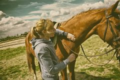 Woman standing next to a horse. Young woman is standing next to a brown horse and stroking him right before taking a horse ride. Authentic emotions of Royalty Free Stock Photography
