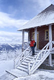 Woman standing next to the house in a mountainous region.  Royalty Free Stock Photos