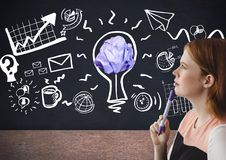 Woman standing next to light bulb with crumpled paper ball in front of blackboard Royalty Free Stock Images