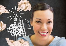 Woman standing next to light bulb drawings with crumpled paper balls in front of blackboard Royalty Free Stock Photography