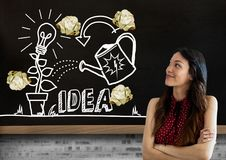Woman standing next to light bulb and ideas drawings garden with crumpled paper balls in front of b Stock Photography