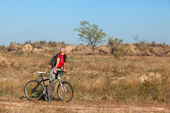 Woman standing next to a mountain bike and looking at the camera Royalty Free Stock Images