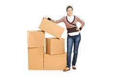 Woman standing next to a pile of carton boxes Stock Photos