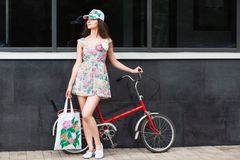 Woman standing next to retro bicycle. Pretty young woman standing next to retro bicycle Stock Image