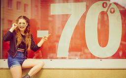 Woman standing next to sale sign. Fashionable woman looking at 70 percentage sale marketing sign. Female wants to buy something at shop Royalty Free Stock Photos