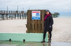 Woman standing next to sign warning No Lifeguard with ocean and pier in background stock photo